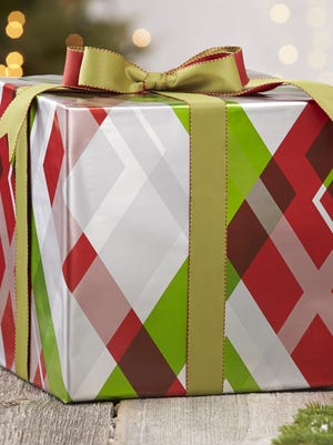 "This photo provided by Crate and Barrel shows a package in holiday plaid gift wrap. Plaids are having a fashion moment as retailers and designers play with the classic pattern, but the apparel and footwear industries are sharing the love as fresh takes on plaid have made headway in housewares and home decor. ""The great thing about plaid is that you can take it in so many different directions,"" said Kristen Chalupa, a kitchen and tabletop product manager for Crate & Barrel. (Crate and Barrel via AP)"