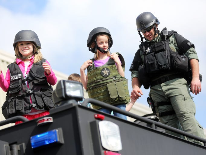 Thanks to her grandfather John winning an auction, Madison Hoffmeister, center, gets a ride to Gubser Elementary in a SWAT vehicle, and her second-grade classmates get to meet Cito the K-9.
