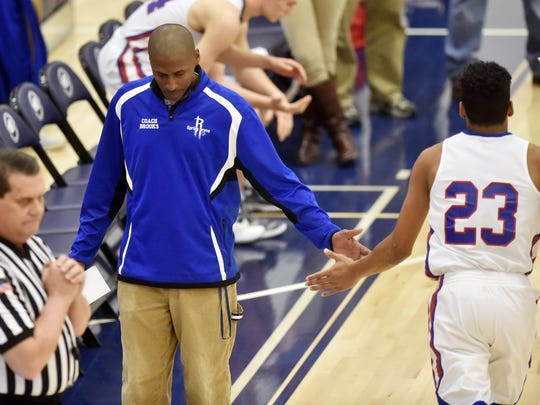 Spring Grove head coach James Brooks greets his son and starter Eli Brooks before a game in March.