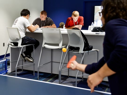 From left, Penn State York sophomores York Wang, Jedidiah Lieberknecht and Cody Inch prepare for a calculus class as Sina Ali Ghourchi plays ping pong in the newly renovated and expanded Joe and Rosie Ruhl Student Community Center. The center reopened Wednesday after the completion of the $13.5 million project.