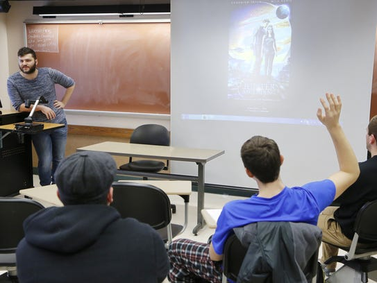 Graduate student Ryan Buss, left, leads a discussion