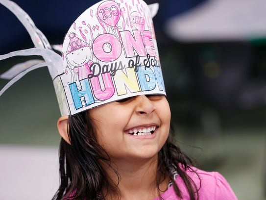 Pai Patel, 6, giggles as her hat to commemorate the