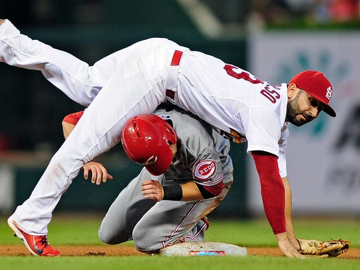 St. Louis Cardinals second baseman Daniel Descalso (33) falls onto Cincinnati Reds shortstop Zack Cozart (2) to complete the double play during the fifth inning at Busch Stadium.
