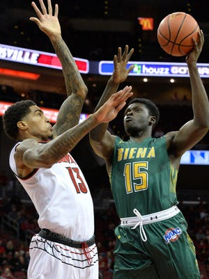 Siena forward Prince Oduro (15) shoots over the defense of Louisville forward Ray Spalding (13) during the first half of an NCAA college basketball game, Wednesday, Dec. 6, 2017, in Louisville, Ky. (AP Photo/Timothy D. Easley)