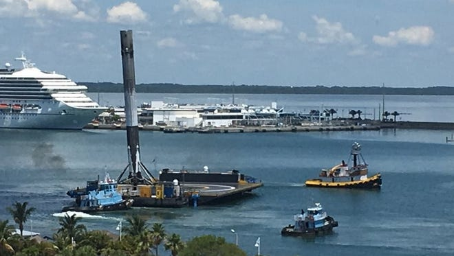 "A tugboat this afternoon towed a SpaceX ""drone ship"" and Falcon 9 rocket booster into Port Canaveral, nearly six days after the rocket launched a communications satellite from Cape Canaveral Air Force Station."