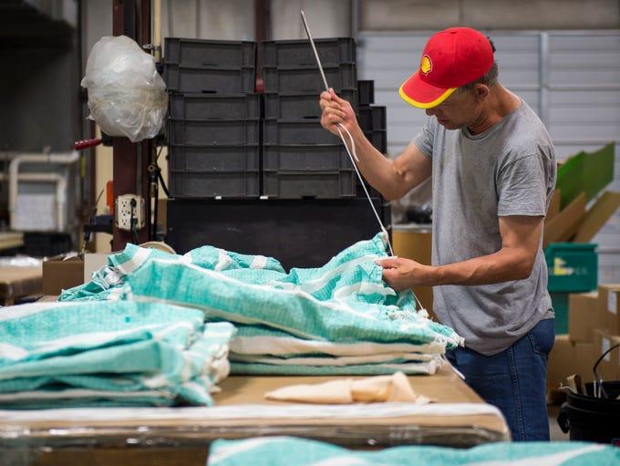 Mark Campbell works to make drawstring bags at Sunshine