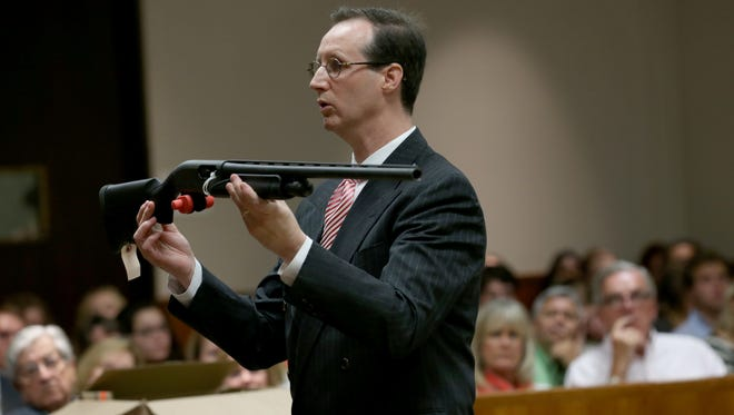 """Monroe County Assistant District Attorney, William Gargan, holds the shotgun that allegedly killed """"Jim"""" Tan. """"Charlie Tan is the one who fired this gun. Charlie Tan solved this problem."""""""