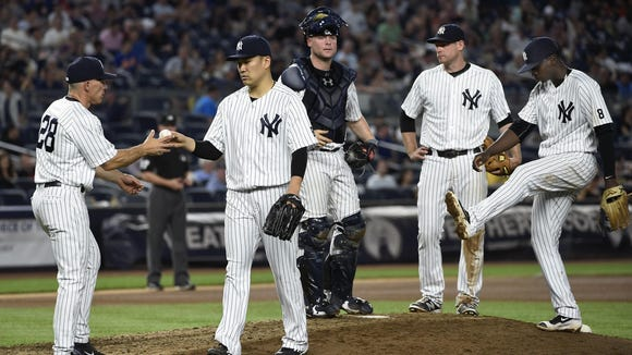 New York Yankees manager Joe Girardi takes the ball from starting pitcher Masahiro Tanaka as catcher Brian McCann, third baseman Chase Headley, second from right, and shortstop Didi Gregorius wait on the mound in the seventh inning of Saturday night's game against the Detroit Tigers.