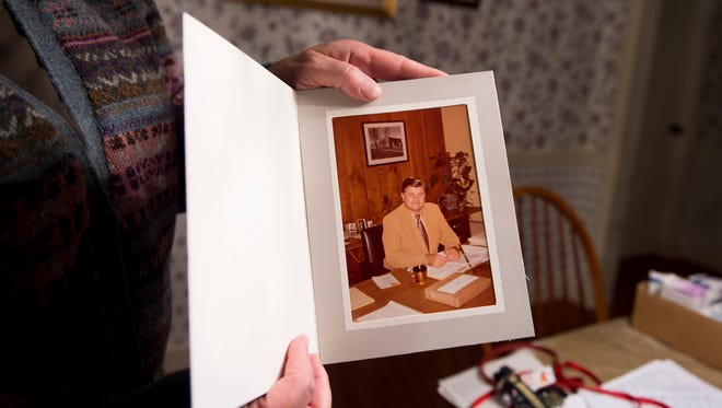 Laura Silver holds up a photo of her late father, Richard Weaver, who died in January. Weaver, pictured behind his desk, worked at R.S. Noonan Inc., in York for 38 years. Active in the Hanover community, Weaver was a member of the Eagle Fire Co. and the Hanover Barbershop Chorus, among other organizations, and was a borough councilman for seven years.