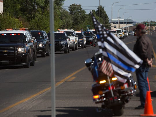 Bobby Jakcsy, with the Patriot Guard Riders, stands with his motorcycle on El Paseo Road as the memorial processional for fallen peace officers makes its way to the Las Cruces Convention Center, where a memorial service was held to commemorate officers who have died in the line of duty, Tuesday May 9, 2017.