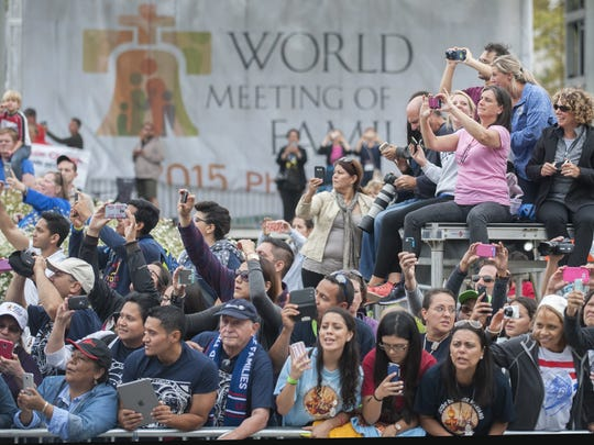 Crowd members await the arrival of Pope Francis prior to Sundays mass on the Benjamin Franklin Parkway in Philadelphia.  09.27.15
