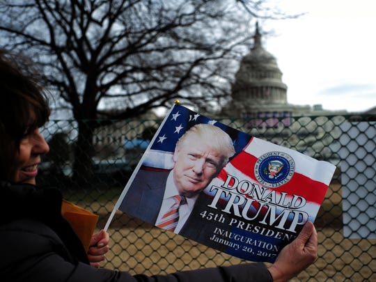 Third-grade school teacher Kimi Moro from California poses with a flag featuring picture of US President-elect Donald Trump near the Capitol Building in Washington, DC, on January 19, 2017, where final preparations are underway a day ahead the inauguration of the 45th President of the US.