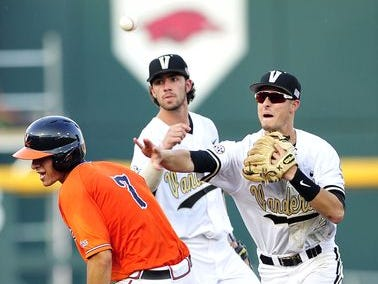 Vanderbilt's Tyler Campbell's (2) throw to first hits the helmet of Virginia's Adam Haseley (7) at second during the third inning.