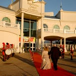 A couple walks down the red carpet as the River City Drum Corp performs at the Kentucky Derby Museum's Derby Gala.  Proceeds from Gala will benefit the Museum's Education programing.  April 25, 2014