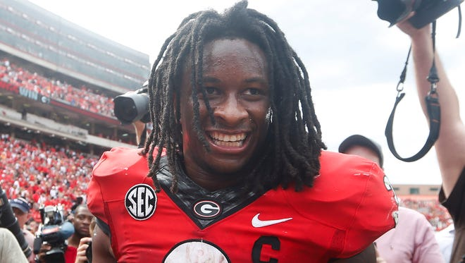FILE - In this Sept. 27, 2014, file photo, Georgia running back Todd Gurley (3) celebrates with linebacker Amarlo Herrera (52) after an NCAA college football game against Tennessee in Athens, Ga. No. 9 Georgia plans to protest following the NCAA decision to bench Gurley for Saturday's game against Florida.