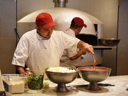 Jose Gonzales prepares to put pizza sauce on fresh dough in the open kitchen that also houses a 1,000-degree Italian oven.