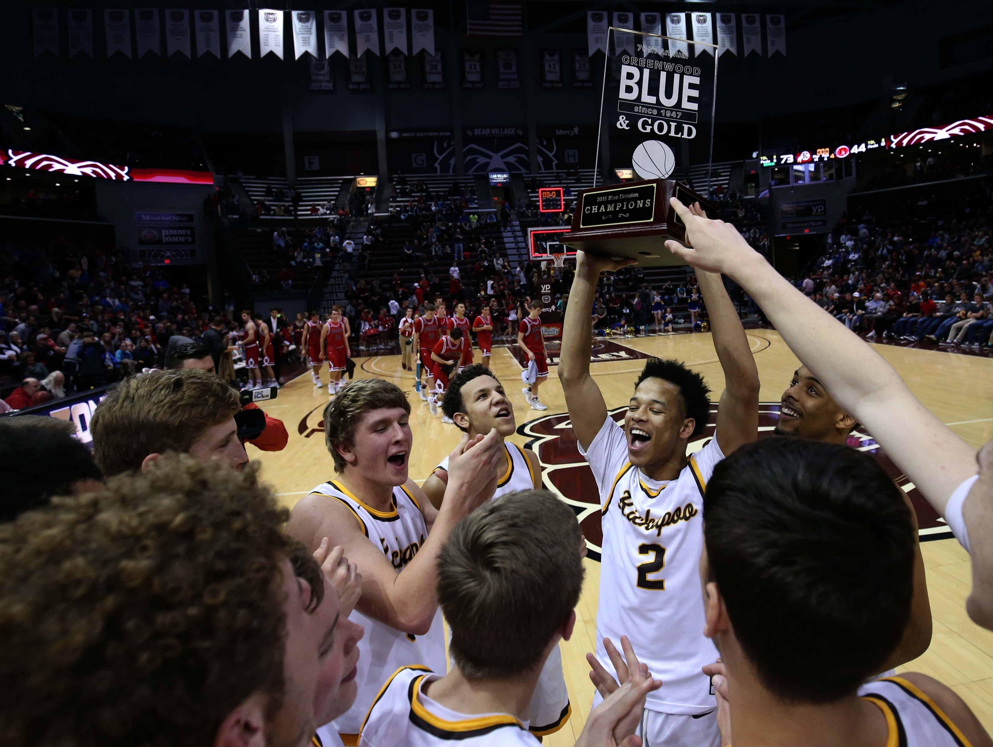 Kickapoo's Derrick Roberson hoists the championship trophy after beating Ozark in the Blue Division Final at JQH Arena on December 30, 2015.