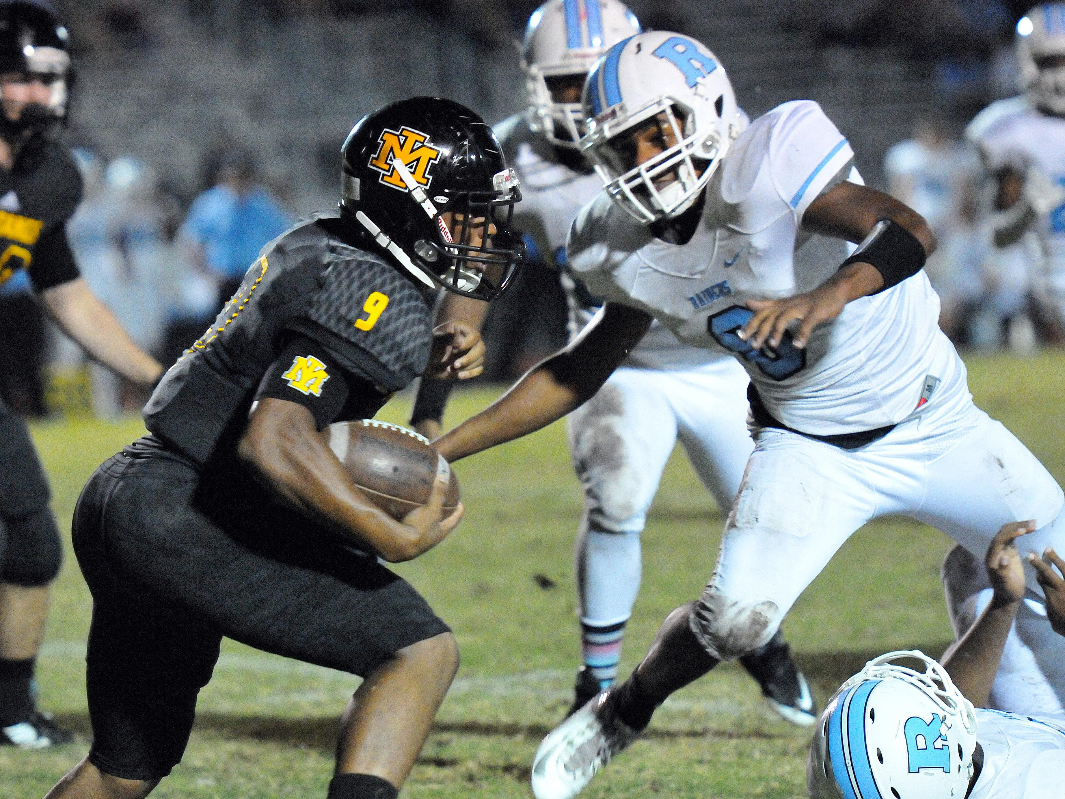 Merritt Island's Taquaan Pratt (9) finds some daylight past Rockledge High defenders during Friday night's game held at Mustang Stadium.