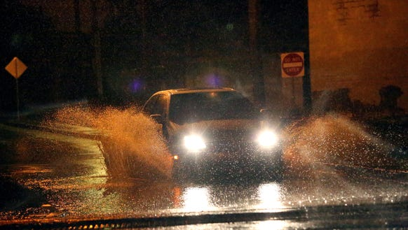 A vehicle passes through a flooded portion of Goss