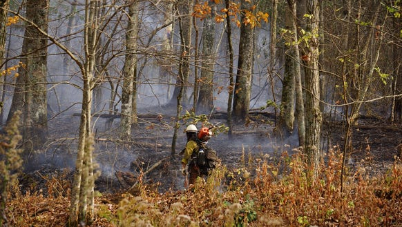 A firefighter patrols a containment line on the Wine
