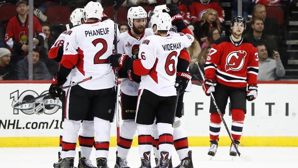 Ottawa Senators players celebrate a goal by defenseman
