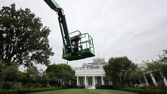 An articulating boom lift hovers over the Rose Garden