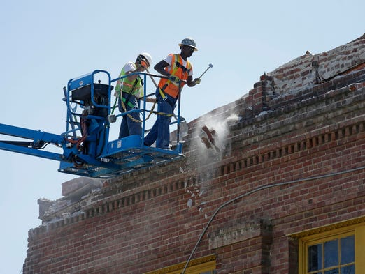 Contractors pull loose bricks from the roof of an earthquake-damaged building on Mare Island in Vallejo, Calif.