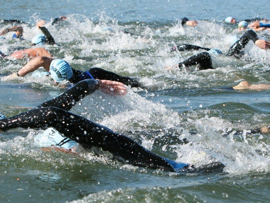 Swimmers churning up the water at a local triathlon.
