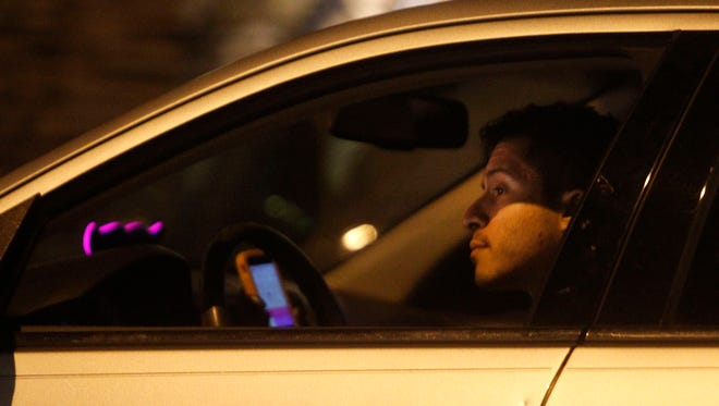 Lyft driver Jason Elizalde waits Friday to pick up a rider on Fourth Street in Austin. Uber and Lyft suspended service in Austin after voters there decided not to overturn city requirements for drivers of ride-hailing companies that include undergoing fingerprint-based background checks.