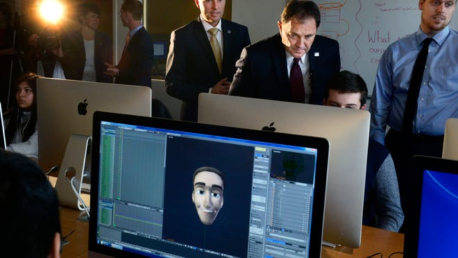 Utah Gov. Gary Herbert leans in to take a look at what student Tyson Parsons is creating in Brian Ericson's, right, 3D Animation class at Salt Lake Community College, Wednesday, Dec. 9, 2015, in Salt Lake City. At left is Lt. Gov. Spencer Cox. Herbert later introduced his recommendations for the fiscal year 2017 budget at SLCC.