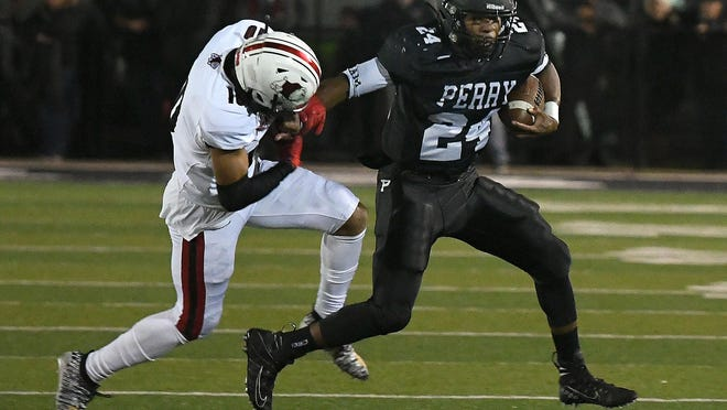 Perry running back Joshua Lemon (24) tries to fight off McKinley safety Brian Pinkney during last year's game at Perry.