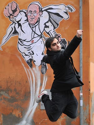 """A tourist jumps for a picture in front of a street art mural showing Pope Francis as a superman, flying through the air with his white papal cloak billowing out behind him and holding a bag bearing the word """"Values"""", by Italian street artist Maupal in downtown Rome near the Vatican on January 29, 2014. The image, created by Italian street artist Maupal, was tweeted yesterday by the Vatican communication twitter account ( @PCCS_VA ). Flying forward with his fist raised, the heroic pontiff -- crucifix swinging in the wind -- carries his trademark black bag, with the word """"values"""" written across it in white.   AFP PHOTO / TIZIANA FABITIZIANA FABI/AFP/Getty Images ORIG FILE ID: 526502785"""