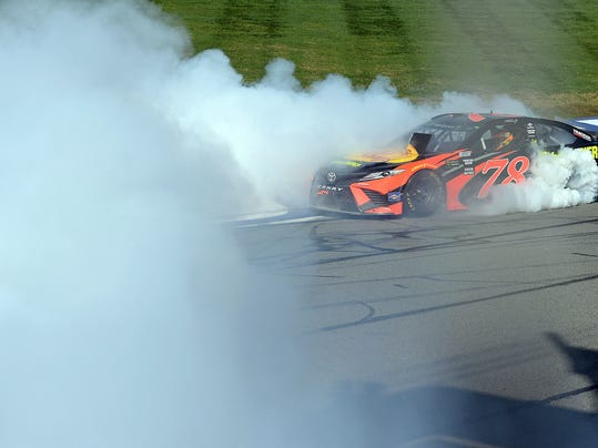 Martin Truex Jr. celebrates with a burnout after winning the NASCAR Cup Series auto race Sunday, March 18, 2018, in Fontana, Calif. (AP Photo/Will Lester)