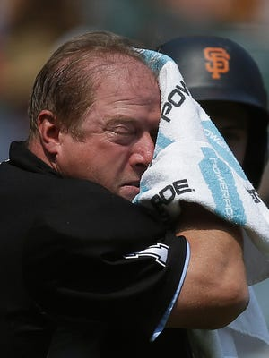 Home plate umpire Bruce Dreckman wipes his face with a towel in the middle of the fourth inning of a baseball game between the St. Louis Cardinals and the San Francisco Giants on Saturday in San Francisco. The Western United States baked through the unofficial end of summer, as temperatures in some parts threatened to peak Saturday at levels not seen in decades.