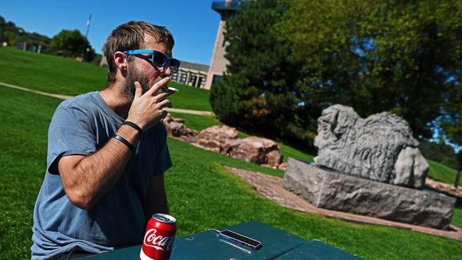 Daniel Eastman, 30, of Sioux Falls, smokes a cigarette Monday, Sept. 19, 2016, at Falls Park in Sioux Falls. The Sioux Falls City Council's land use committee will hear a proposal Tuesday for an outdoor smoking ban on all publicly owned property, including Falls Park, in Sioux Falls.