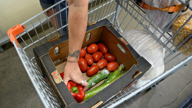 A woman shops the Food Share program at the Food Bank for Larimer County on Monday, August 22, 2016.