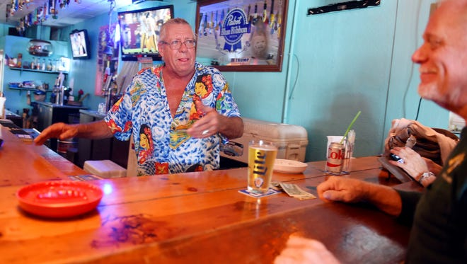 "Randy Dehmer, owner of Uncle Sam's Brau Haus in Vero Beach, talks Saturday, Sept. 9, 2017, with patron Tim Parsons. ""We have been open every single day since we first opened the doors ten years ago,"" Dehmer said. ""It doesn't matter if the place is half under water, we'll give you a personal flotation device so you can belly up to the bar."""
