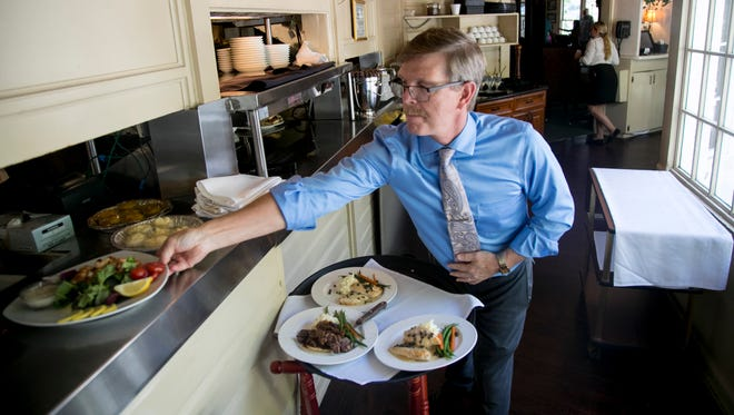 Manager Denny Genge readies trays for servers during the lunch rush at The Veranda in downtown Fort Myers on Thursday.