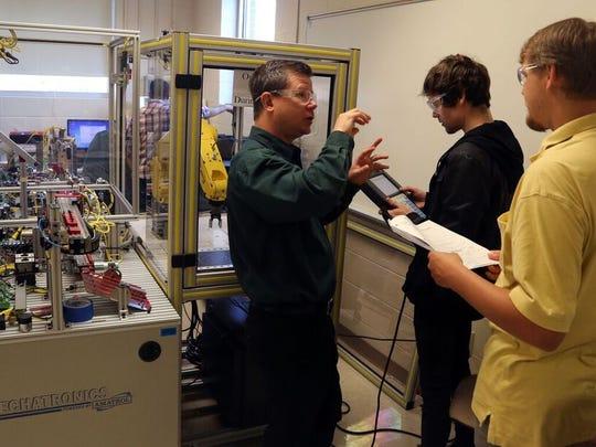 Shane Buchanan, director of Motlow State Community College's mechatronics program, instructs students Nate Shaw and John Trent.