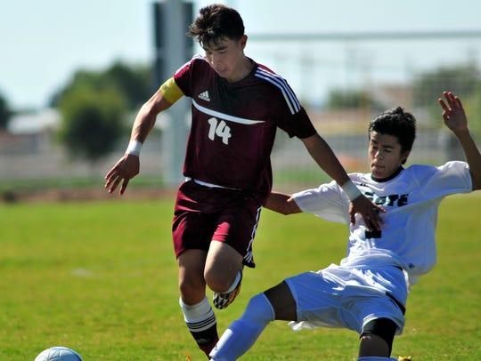 Gadsden's Marvin Rivas (14) gets around a sliding Manuel