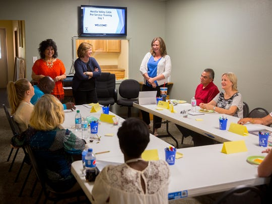 Mesilla Valley CASA staff and volunteers gather at the CASA offices for the beginning of 30 hours of training in April 2016. Doreen Gallegos is at the head of the table in a red shirt. Brandie White is in white cardigan at head of table. Training sessions are now done by videoconferencing.