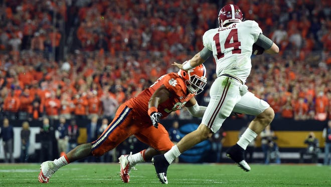 Alabama Crimson Tide quarterback Jake Coker (14) runs away from Clemson Tigers defensive end Kevin Dodd (98) in the second quarter in the 2016 CFP National Championship.