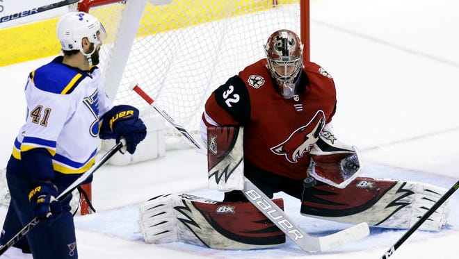 Coyotes goaltender Antti Raanta (32) makes the save in front of St. Louis Blues defenseman Robert Bortuzzo in the third period during a 6-0 Coyotes win on Saturday at Gila River Arena in Glendale. (AP Photo/Rick Scuteri)