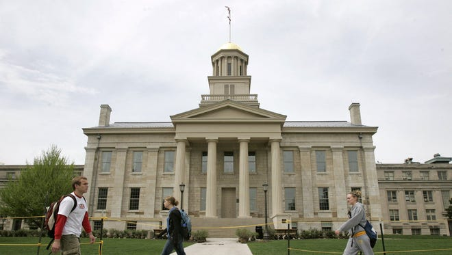 University of Iowa students walk past the Old Capitol building in Iowa City, Iowa.