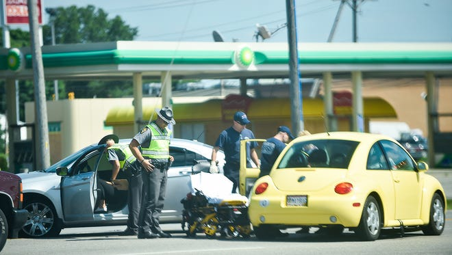 Ohio Highway Patrol officers inspect a two-car crash near the intersection of Barks Road and Delaware Avenue.