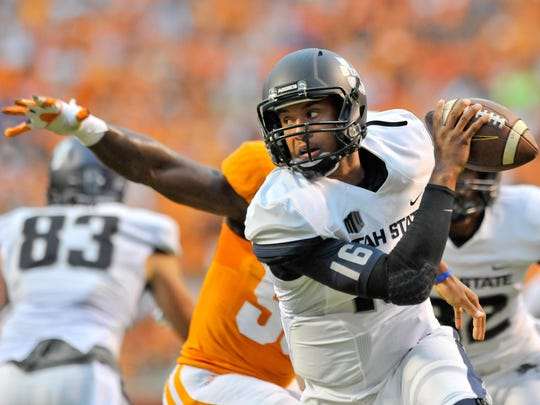 Utah State Aggies quarterback Chuckie Keeton (16) scrambles to avoid the sack against the Tennessee Volunteers during the first half at Neyland Stadium.