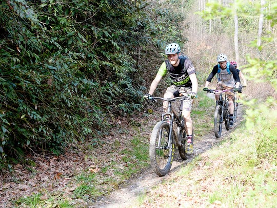 Mountain bikers ride on the Davidson River Trail April 3, 2018.