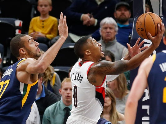Portland Trail Blazers guard Damian Lillard (0) lays the ball up as Utah Jazz center Rudy Gobert (27) defends in the first half during an NBA basketball game Wednesday, Nov. 1, 2017, in Salt Lake City. (AP Photo/Rick Bowmer)