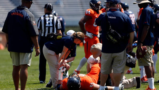 Virginia head coach Mike London (left) and team trainers look over Cody Wallace after he was injured during the team's spring game.