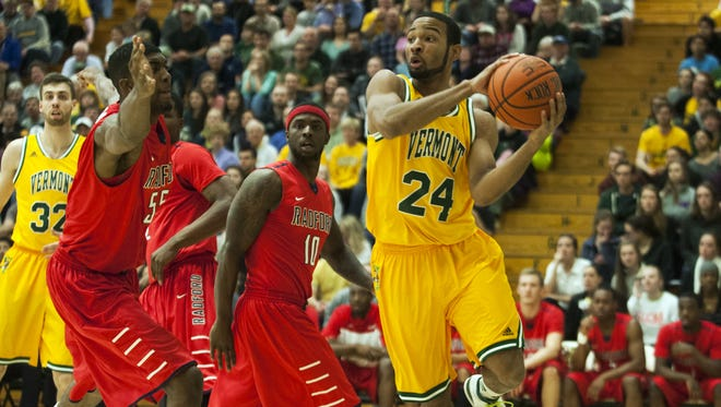 UVM guard Dre Wills (24) looks to pass the ball during the College Basketball Invitational game between the Radford Highlanders and the Vermont Catamounts at Patrick Gym on Monday night.